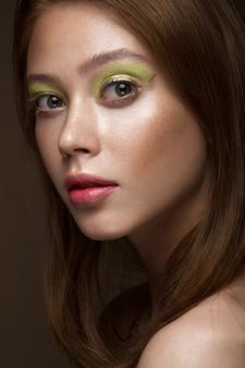 Красивая рыжеволосая девушка с креативным зеленым макияжем