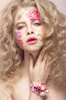 Красивая блондинка с локонами и цветочным узором на лице. салон цветов.