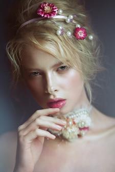 Красивая модная блондинка с цветами на шее и в волосах, мокрый обнаженный макияж