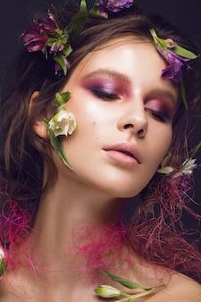 Красивая девушка с художественным макияжем и цветами