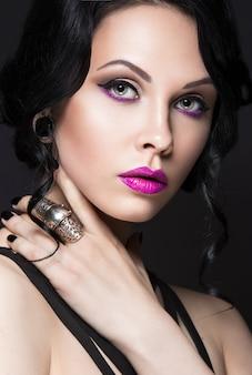 Красивая девушка в готическом стиле с кожаными аксессуарами и ярким макияжем.