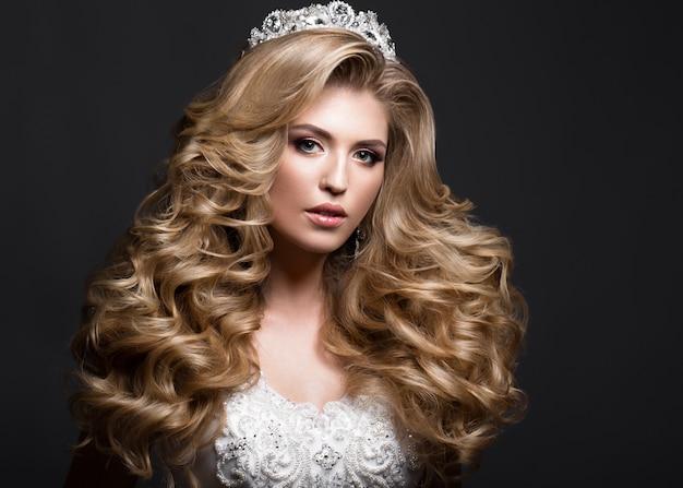 カールと王冠の結婚式のイメージの美しい金髪の花嫁。美容顔。