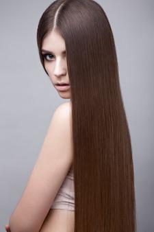 完全に滑らかな髪と古典的なメイクと美しいブルネットの女性