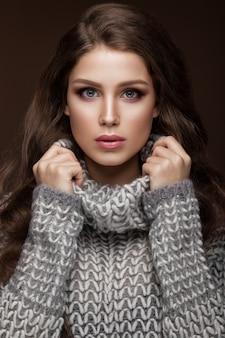 暖かいセーターと長いストレートの髪で穏やかなメイクと美しい若い女性
