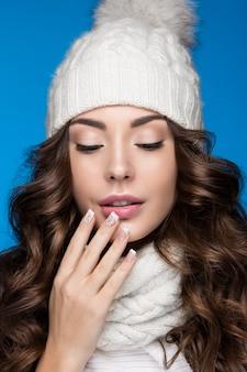 Красивая женщина с нежным макияжем, дизайнерским маникюром и улыбкой в белой вязаной шапке