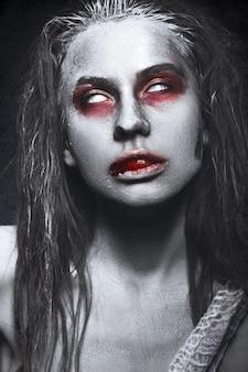 ゾンビの形の女の子、彼の唇に血でハロウィーンの死体