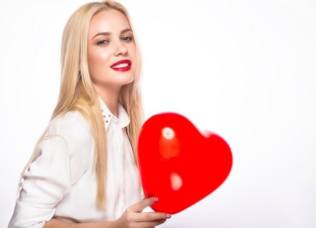 Портрет красивой белокурой женщины с ярким макияжем и красным сердцем в руке