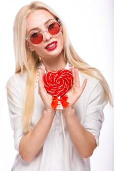 Портрет красивой белокурой женщины с ярким макияжем и красным конфетным сердцем в руке