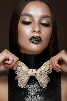 黒の創造的なアートメイクと金のアクセサリーを持つ美しい女性