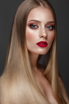 Красивая белокурая девушка с идеально гладкими волосами, классическим макияжем и красными губами. красота лица