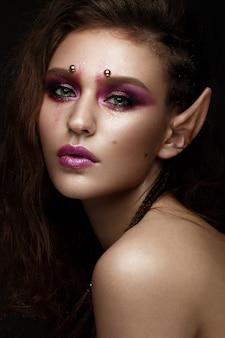 創造的なカラフルなメイクアップを持つ美しい少女。美容顔。