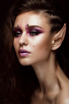 創造的な髪型三つ編み、アートメイク、エルフの耳を持つブルネットの少女。美容顔。