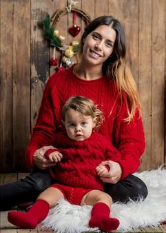 クリスマスの木製の背景に赤いプルオーバーで同様に服を着た美しいママと娘