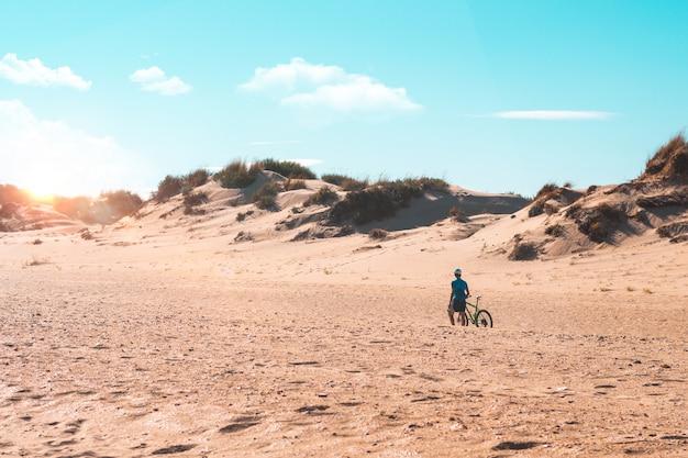 Человек на велосипеде на пляже. спорт и концепция активной жизни в летнее время и на открытом воздухе.
