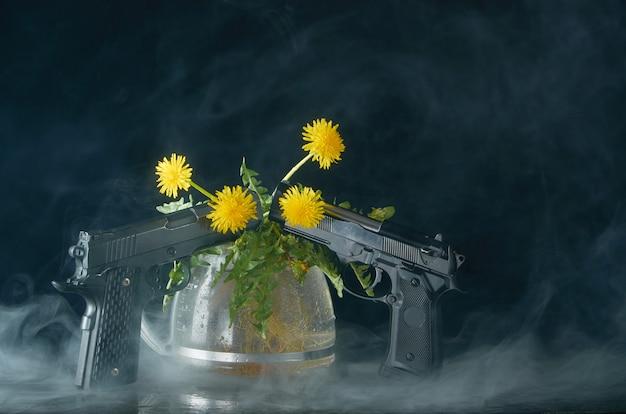 Одуванчик с корнями и листьями в стеклянном чайнике и с двумя пистолетами в дыму