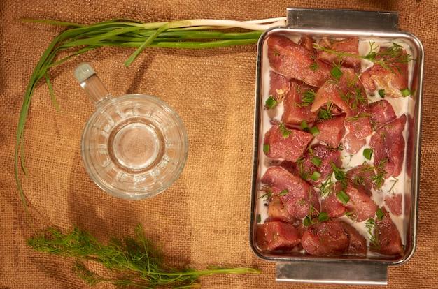 新鮮なハーブとビール用のマグカップが付いた布の上のスチール皿に牛乳と野菜の肉でマリネ