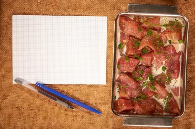 Маринованное мясо с молоком и зеленью в стальном глубоком блюде на домашней ткани с чистым листом бумаги и шариковой ручкой