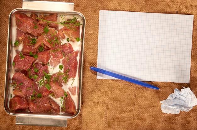 Маринованное мясо в молоке и зелени в стальном глубоком блюде на домашней ткани с чистыми листами бумаги и шариковой ручкой