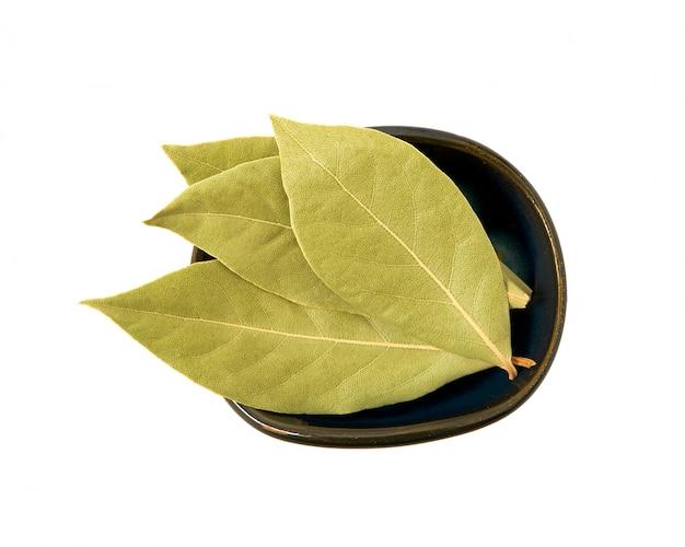 白い背景の上のボウルに月桂樹の葉を乾燥させます。