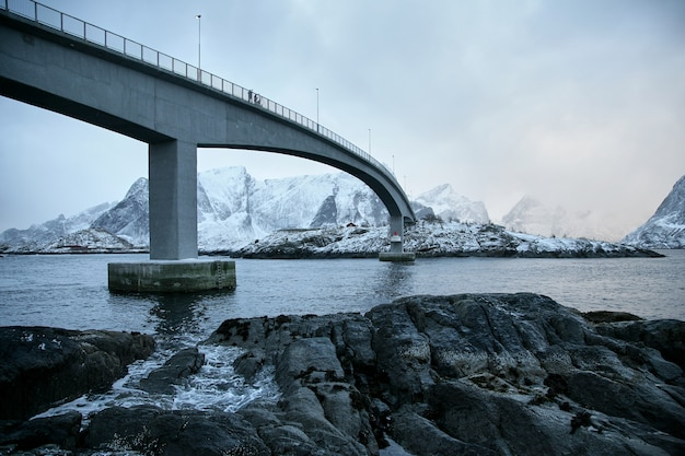 橋の下とノルウェーのロフォーテンにある象徴的なハムノイの写真家と赤い家のロブの写真