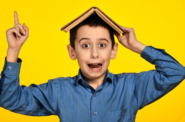 黄色の背景に彼の頭の上の本を持つ陽気な少年