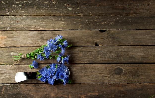 コピースペースを持つトップビューで古い木の板に新鮮な薬草(カモミール、よもぎ、ノコギリソウ、ミント、セントジョンズワート、チコリ)