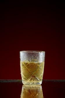 Стакан с оригинальным алкогольным напитком с мятой и льдом на красном