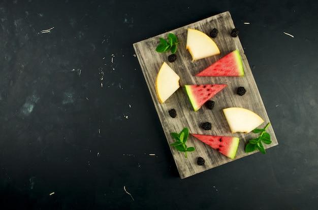 メロン、スイカ、ブラックベリー、ミント、木製のテーブル