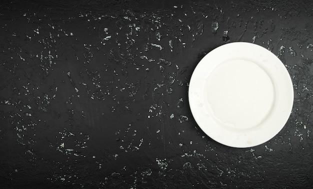 Белая мокрая пустая тарелка на темном столе. вид сверху. копировать пространство