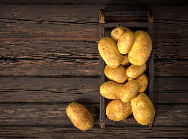 生じゃがいも食品。木製のテーブルの上の古い箱のジャガイモ