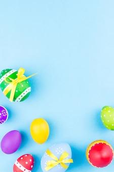 Красочные пасхальные яйца на синем фоне плоской планировки.