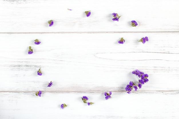 素朴な白い木製の背景に紫の花のフレーム構成