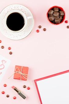 День святого валентина с кофейным напитком, подарочной коробкой, конфетами на пастельно-розовом фоне, плоской планировкой