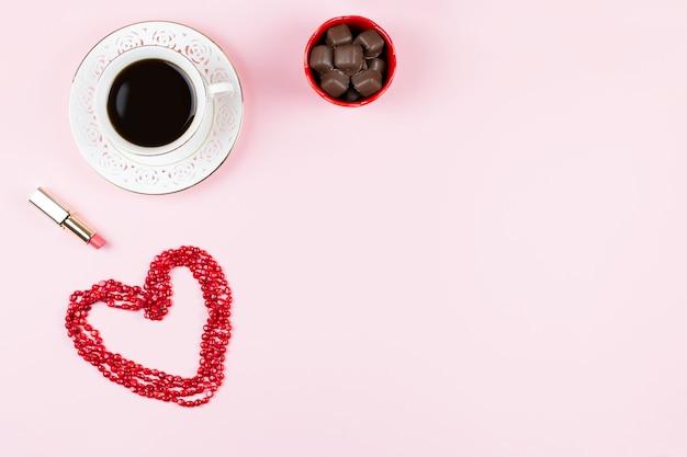 チョコレート菓子、温かい飲み物、口紅。ピンク、赤、白の色の女性の背景。フラット横たわっていた、スペースをコピーします。