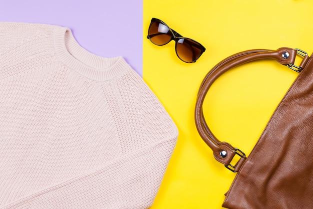 Осенняя женская одежда и аксессуары - розовый свитер, кожаная сумка, солнцезащитные очки.