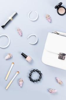 ファッションブロガーワークスペースフラットは、化粧品、財布、プランナー本、花で飾られています。