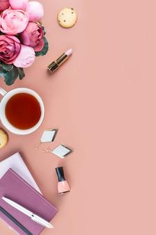 フラットレイアウトのホームオフィスデスク。日記、花、お菓子、ファッションアクセサリーと女性のワークスペース。ファッションブロガーのコンセプト。