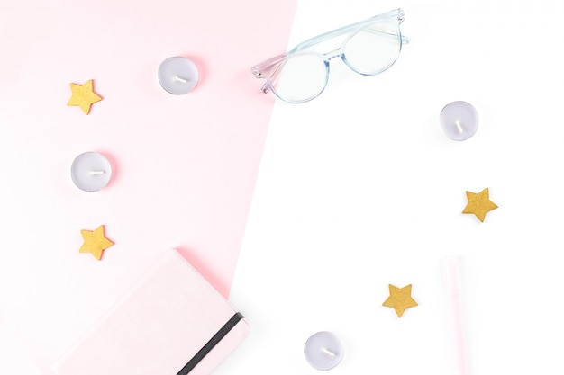 フラットレイアウトのホームオフィスデスク。プランナー、眼鏡、キャンドルで女性のワークスペース。