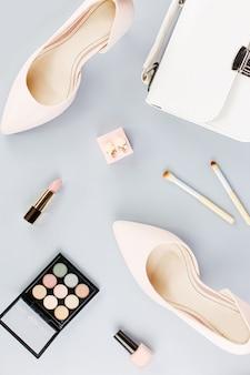 ファッションブロガーワークスペースフラットパンプス、化粧品、財布、プランナー本、花でレイアウト。