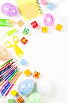 Школьные принадлежности, детское творчество концепции плоской планировки. различные художественные инструменты для детей на белом столе. копировать пространство