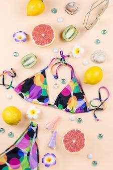 Купальник бикини с соломенной шляпе, цветы и фрукты, концепция лето. пляжное направление, летняя мода