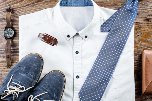 Мужские классические наряды плоской формы с формальной рубашкой, галстуком, туфлями и аксессуарами.