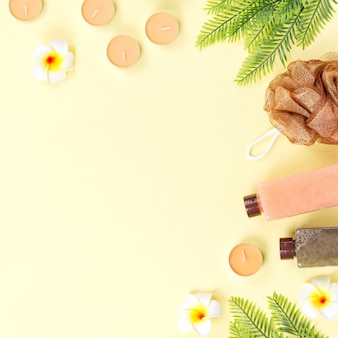 Спа и средства по уходу за телом плоской планировки. скраб для тела, соль для ванн, увлажняющий лосьон, свечи и листья на деревянном фоне