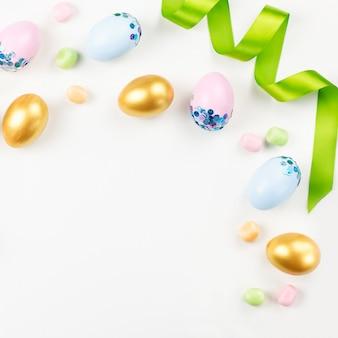 装飾された卵、花、キャンディー、白のパステルカラーのリボンでお祝いイースターの背景。コピースペース