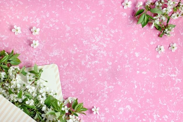 Весенний расцвет. вишневые цветы в конверте коробки плоские на пастельных фоне. открытка с белыми цветами, копией пространства