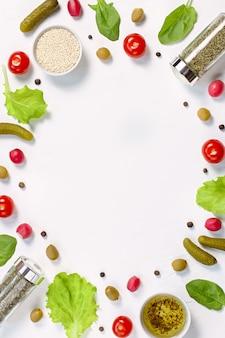 白い机の上のサラダ食材のレイアウト。チェリートマト、きゅうり、野菜、唐辛子、スパイスと食品パターン