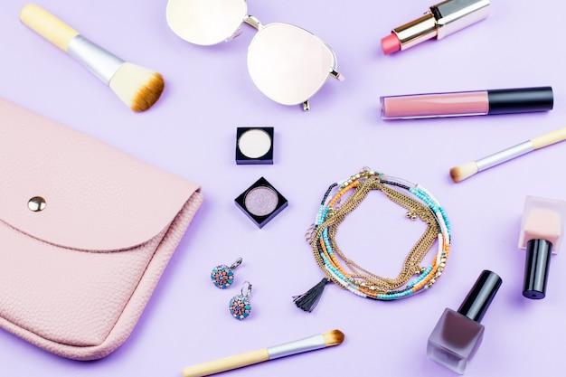 パステル調の背景に女性のファッションアクセサリー。ピンクの財布、ミラーサングラス、ジュエリー、メイクアップアイテム。