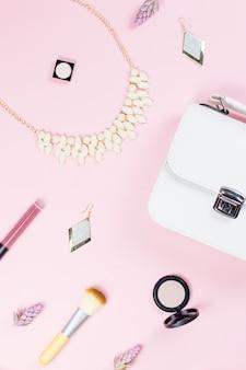 ファッションアクセサリー、化粧品、ジュエリー、パステル調の背景のハンドバッグ。美しさとファッションのコンセプト、フラットレイアウト