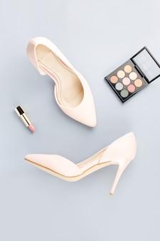 Бледно-розовые женские туфли, помада и палитра теней на сером фоне. мода блоггер концепция плоской планировки.