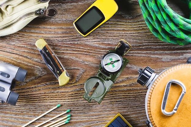 Туризм или путешествия оборудование с сапоги, компас, бинокль, спички на деревянных фоне. концепция активного образа жизни